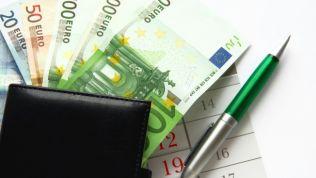 Geldscheine ragen aus dem Geldbeutel. Daneben liegt ein grüner Kugelschreiber