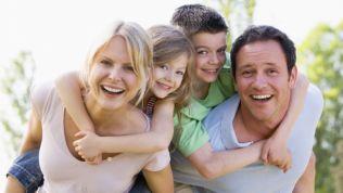 Grinsende Bilderbuchfamilie: Vater, Mutter, Sohn und Tochter im Garten