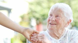 Alte Dame kriegt die Hand einer jungen Frau gereicht.