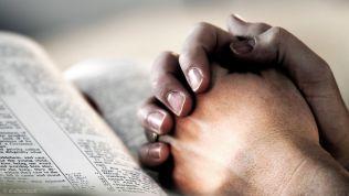 Gefaltete Hände auf einem Buch