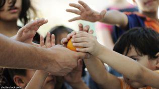 Menschen greifen nach einer Orange