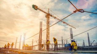 Wirtschaft: Arbeiter auf einer Baustelle mit Kränen