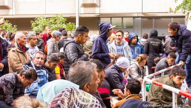 Flüchtlinge warten vor einer Behörde
