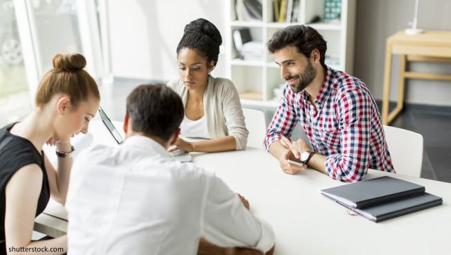 Menschen sitzen um einen Tisch und diskutieren