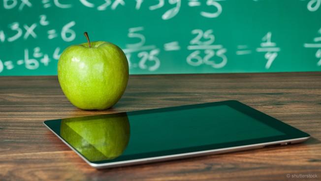 Tablet mit Apfel vor KReidetafel