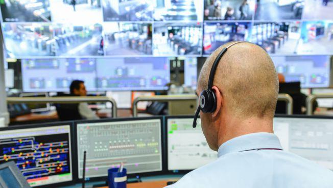 Mann mit Kopfhörern vor Bildschirmwand