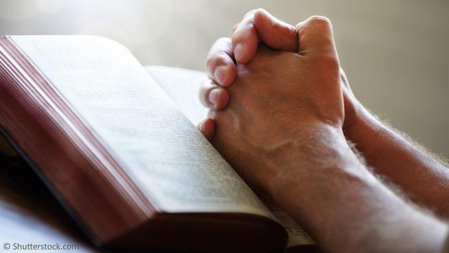 Gefaltete Hände auf einem Gebetbuch