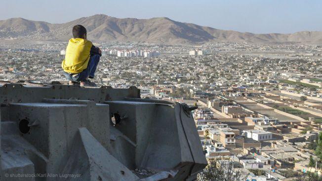 Afghanistan: Junge sitzt auf Panzer und schaut auf Kabul
