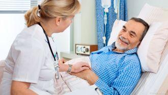 Ärztin am Bett eines Patienten