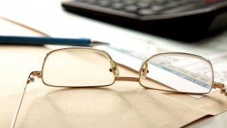 Haushaltsmotiv: Brille, Papierstapel und Taschenrechner